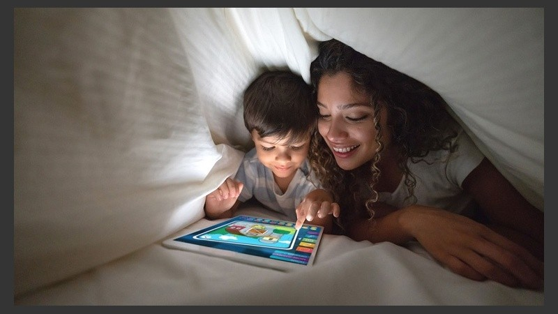 Mother and son playing on a digital tablet in bed