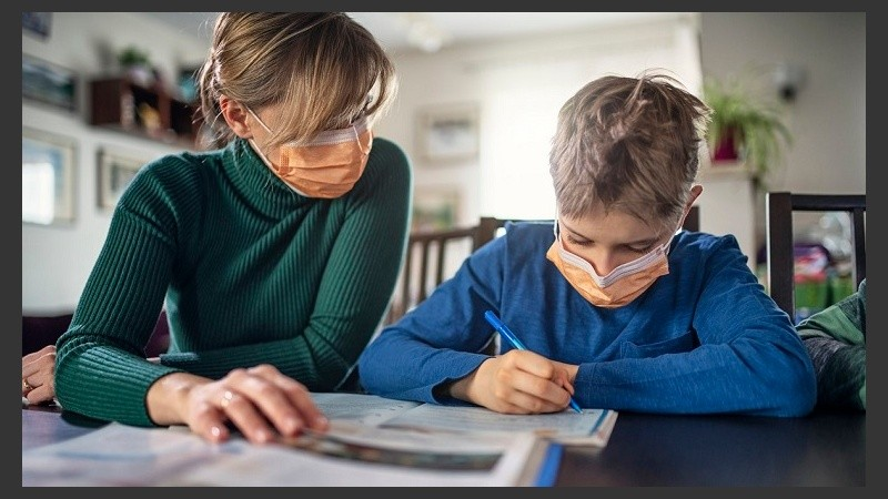 Mother homeschooling her son wearing face masks